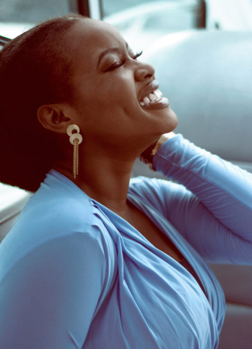 African American woman in blue dress with eyes closed and huge smile