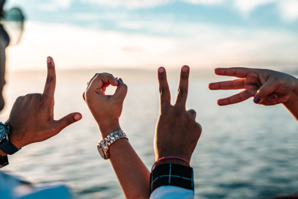 A group of people's hands spelling the word 'love' with their fingers, sea in the background